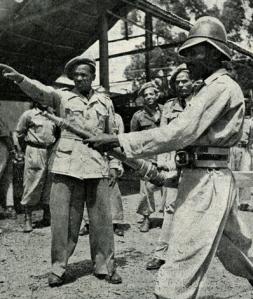 Pompiere etiope con cinturone ed elmo italiano modello Milano nel dopoguerra. I suoi colleghi indossano baschi stile britannico