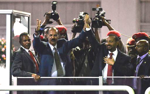 President Isaias Afeworki of Eritrea and Prime Minister Abiy Ahmed of Ethiopia salute the people gathered at the millennium hole to hear speech from the leaders of east African countries in Addis Ababa on July 15, 2018. / AFP PHOTO / MICHAEL TEWELDE
