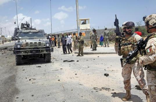 Two members of the Italian military, right, attend the scene after an attack on a European Union military convoy in the capital Mogadishu, Somalia Monday, Oct. 1, 2018. A Somali police officer says a suicide car bomber has targeted a European Union military convoy carrying Italian military trainers in the Somali capital Monday. (ANSA/AP Photo/Farah Abdi Warsameh) [CopyrightNotice: Copyright 2018 The Associated Press. All rights reserved.]