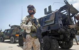 A member of the Italian military stands guard at the scene next to a damaged armored personnel carrier after an attack on a European Union military convoy in the capital Mogadishu, Somalia Monday, Oct. 1, 2018. (ANSA/AP Photo/Farah Abdi Warsameh) [CopyrightNotice: Copyright 2018 The Associated Press. All rights reserved.]