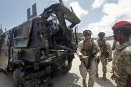 Two members of the Italian military and a Somali soldier, right, walk next to a damaged armored personnel carrier after an attack on a European Union military convoy in the capital Mogadishu, Somalia Monday, Oct. 1, 2018. A Somali police officer says a suicide car bomber has targeted a European Union military convoy carrying Italian military trainers in the Somali capital Monday. (ANSA/AP Photo/Farah Abdi Warsameh) [CopyrightNotice: Copyright 2018 The Associated Press. All rights reserved.]