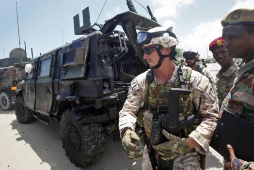 Two members of the Italian military walk past Somali soldiers, right, next to a damaged armored personnel carrier after an attack on a European Union military convoy in the capital Mogadishu, Somalia Monday, Oct. 1, 2018. A Somali police officer says a suicide car bomber has targeted a European Union military convoy carrying Italian military trainers in the Somali capital Monday. (ANSA/AP Photo/Farah Abdi Warsameh) [CopyrightNotice: Copyright 2018 The Associated Press. All rights reserved.]