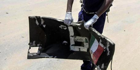 epa07061209 A Somali security officer picks up a piece of the vehicle body with Italian flag at the scene of an explosion in Mogadishu, Somalia, 01 October 2018. A car bomb hit a military vehicle near the Defense Ministry in Mogadishu on 01 October, killing at least one person. EPA/SAID YUSUF WARSAME