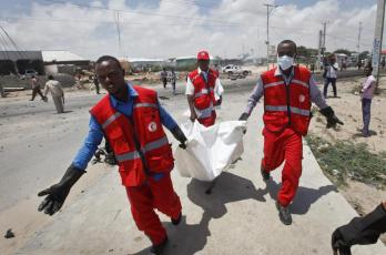Somali Red Crescent workers carry away the body of a Somali civilian after an attack on a European Union military convoy in the capital Mogadishu, Somalia, Monday, Oct. 1, 2018. A Somali police officer says a suicide car bomber has targeted a European Union military convoy carrying Italian military trainers in the Somali capital Monday. (ANSA/AP Photo/Farah Abdi Warsameh) [CopyrightNotice: Copyright 2018 The Associated Press. All rights reserved.]